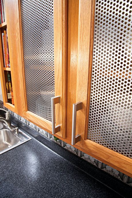Close up view of McNICHOLS Round Hole Perforated Metal cabinet inserts in a kitchen in Woodmere, NY