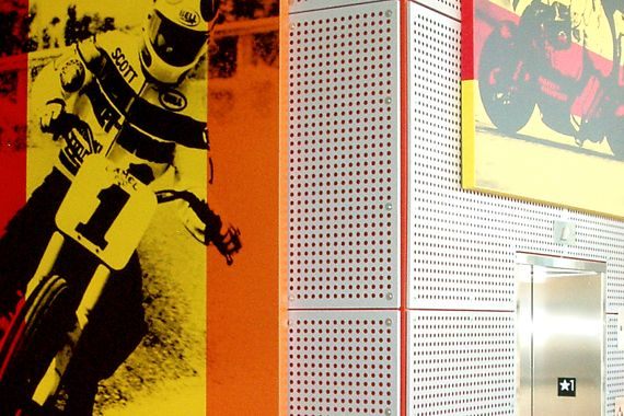 Motorcycle pictures hung on wall of Perforated Metal panels