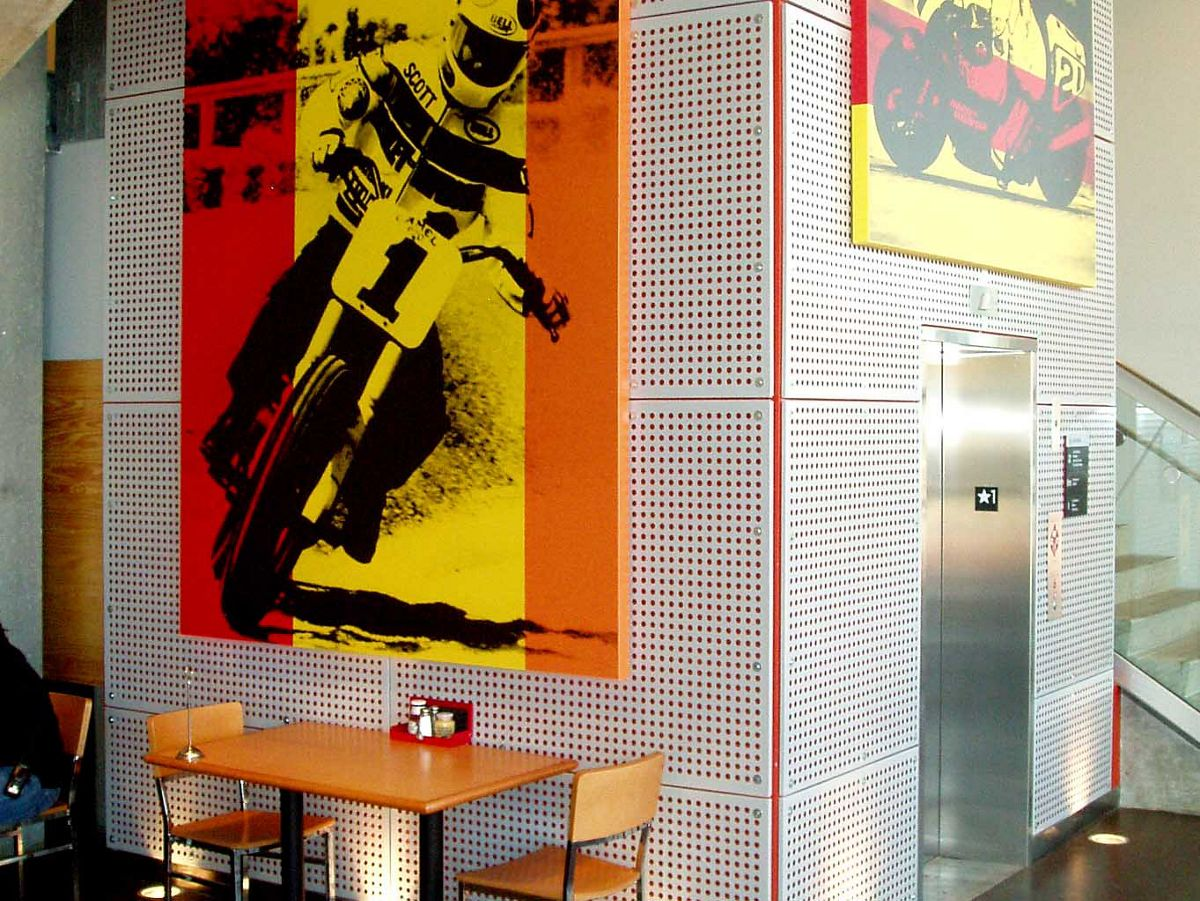 Canvas with man riding a motorcycle hung on a wall of Perforated Metal panels inside a cafe